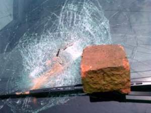 Throwing a brick at a passing car.