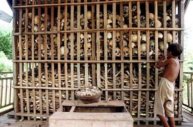 The Killing Fields of Cambodia: a file photo taken 17 September 1995 shows a Cambodian boy examining the skeletal remains of some 2,000 victims of the Khmer Rouge regime at a memorial stupa in northwest Cambodia.  Victims' bones are kept in makeshifts memorials throughout Cambodia as a remembrance of the millions who died under the 1975-1979 Khmer Rouge rule, led by the infamous Pol Pot, whom military officials reported 16 April to have died of a heart attack while in the Cambodian mountains 15 April.