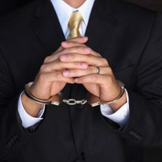 Handcuffed white collar criminal from the corporate world.