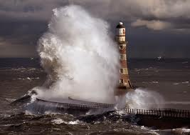 A Lighthouse manages to stand tall even tossed about in a stormy sea.